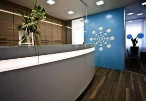 Empfangstheke neue Arztpraxis mit Wandverkleidung und Praxislogo passend zu Corporate Design